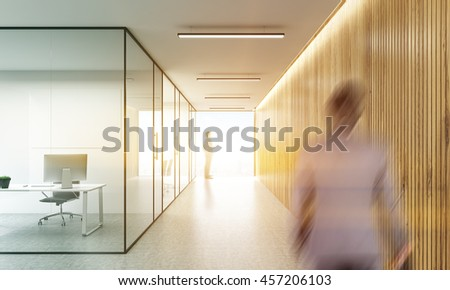 Side view of blurry businesspeople in office interior with blank whiteboard behind glass doors and hallway with wooden wall and sunlight. Mock up, 3D Rendering