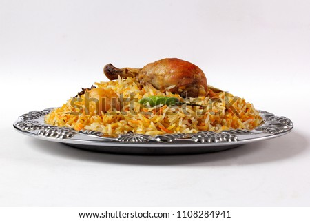 Side view of bombay biryani in silver plate, Traditional spicy indian food, Iftar meal, Ramadan dinner on white background.