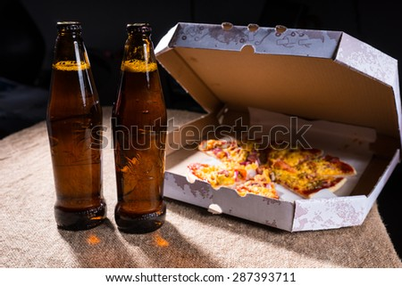 Side View of Bottles of Beer on Burlap Covered Table Beside Cardboard Take Out Box of Pizza with Open Lid