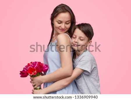 Side view of boy embracing mother from back while congratulating with 8 March and giving bouquet of tulips on pink backdrop  #1336909940