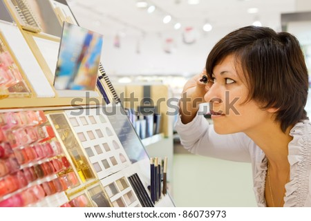 Side view of   brunette woman chooses mascara at cosmetics  shop
