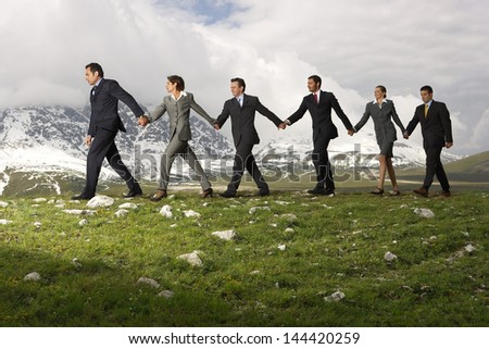 Side view of business people holding hands and walking through mountains