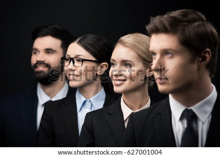 side view of business people standing in row isolated on black #627001004