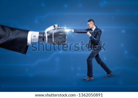 Side view of businessman fighting big robot hand, bright white spark appearing at place where they touch. Human mind vs artificial intelligence. Professional rivalry. Struggle for success. #1362050891