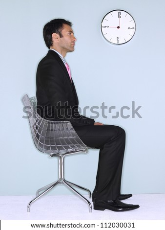 Side view of businessman sitting on chair with wall clock in background