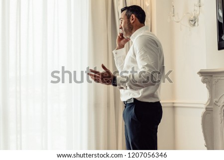 Side view of businessman talking on mobile phone while standing in hotel room. CEO having an important discussing over phone. #1207056346