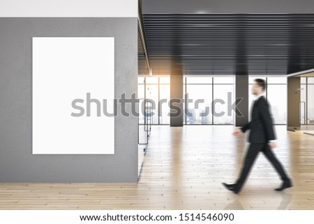 Side view of businessman walking in contemporary office interior with empty poster, city view and daylight. Mock up, #1514546090