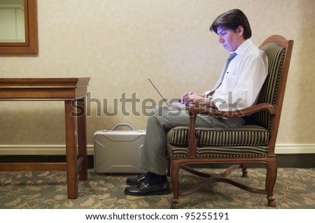 Side view of businessman working on laptop