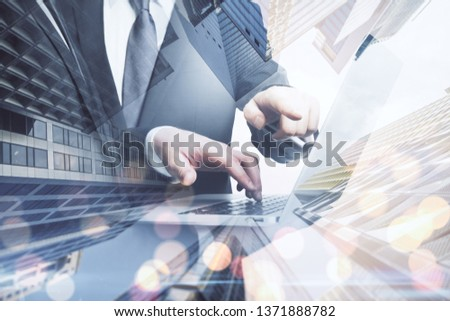 Side view of businessmen hands using laptop together on blurry bokeh city background. Teamwork and communication concept. Double exposure  #1371888782