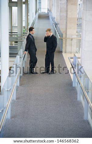 Side view of businessmen standing in office hallway