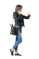 Side view of busy casual fashion girl on the phone checking time on her watch. Full body length portrait isolated over white background