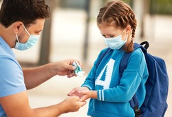Side view of careful dad in protective mask pouring sanitizer into hands of little school aged daughter during coronavirus pandemic