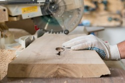Side view of carpenter cutting with  radial arm saw. Woodworker using electric jigsaw in workshop for  production of wooden furniture. Joinery work concept. Close up