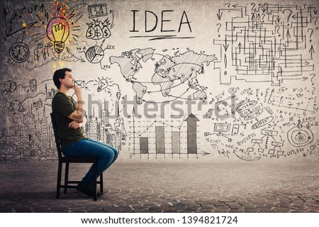 Side view of casual guy seated on a chair keeps hand under chin thoughtful looking away, has a lot of plans and goals as business sketch on grey background. Uniqueness of the idea and genius concept.