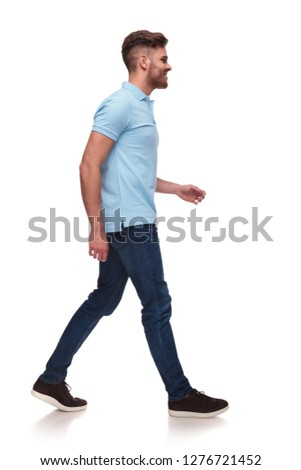 side view of casual man in blue polo shirt walking on white background and smiling, full body picture