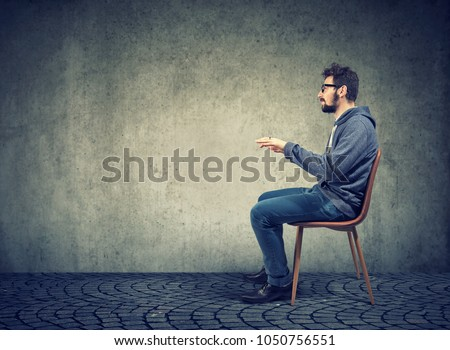 Side view of casual man sitting at invisible table pretending to type on computer.  #1050756551