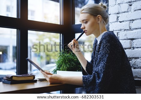 Side view of casual young female student biting pen while watching tablet pensively, she preparing for entrance examination in college. Woman recreating in coffee shop with favourite book