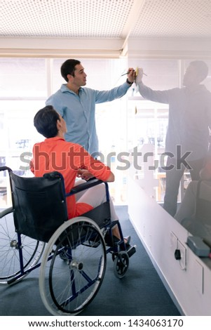 Side view of Caucasian business executives discussing over glass board in a modern office. Disabled female executive sitting in wheelchair. #1434063170