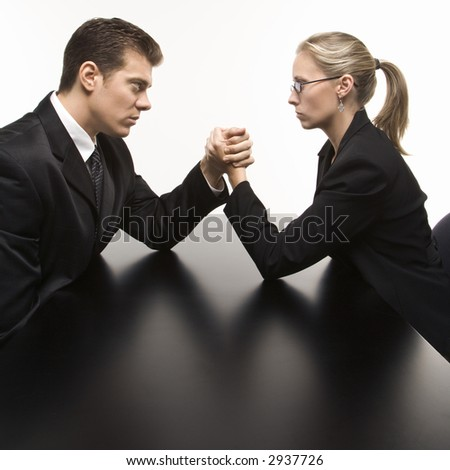 Side view of Caucasian mid-adult businessman and businesswoman arm wrestling on table.