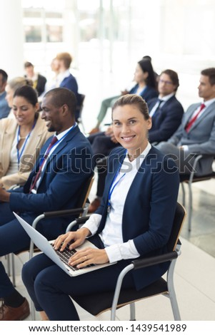 Side view of Caucasian young female executive using laptop in conference room, smiling to camera. With executives in the background. #1439541989