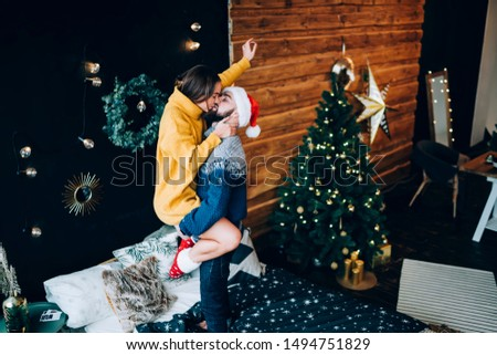 Side view of cheerful affectionate couple in warm woolen clothes and red hat having fun and kissing tenderly near Christmas tree, wreath and lights in cosy room