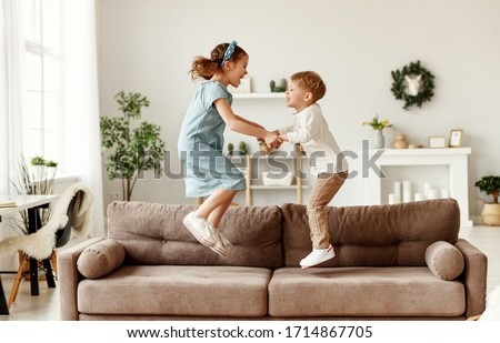 Side view of cheerful boy and girl holding hands and jumping on couch while having fun at home together