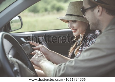 Side view of cheerful happy young girlfriend and boyfriend are using their car navigation system to get to their final destination. Girl is expressing gladness