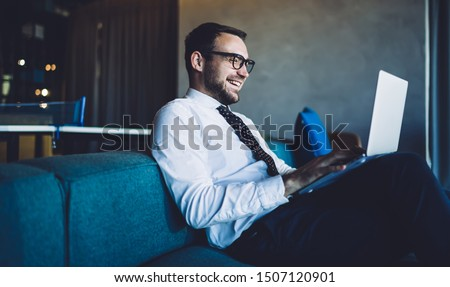 Side view of cheerful professional expert of business marketing reading positive received email from client using 4g connection on laptop computer, happy man in formal wear browsing web page