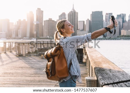 Side view of cheerful woman traveller with touristic backpack enjoying American getaway posing for clicking selfie picture with retro instant camera, concept of happiness and vacations #1477537607