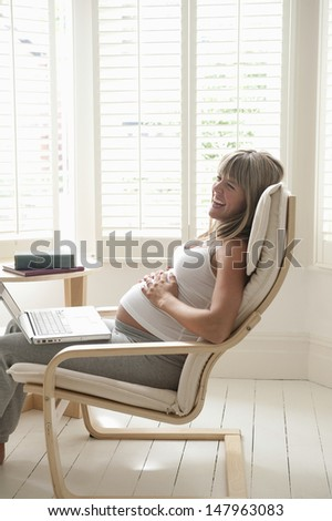 Side view of cheerful young pregnant woman with laptop on chair