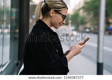 Side view of cheerful young woman blogger laughing while chatting online in social networks on modern smartphone using 4G internet.Positive hipster girl holding cellular and reading news on website