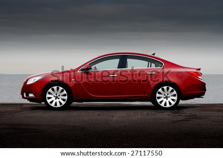 Side view of cherry red business sedan parked on a sea coast