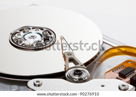 side view of chrome hard drive with a white background; orange communications ribbon and board adds nice contrast to the hard drive