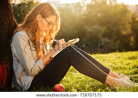 Side view of concentrated brunette woman in eyeglasses sitting near the tree in park and writing something on notebook