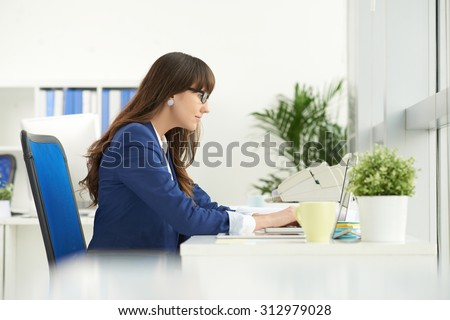 Side view of concentrated business lady working on laptop at the table