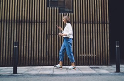 Side view of concentrated female pedestrian in stylish outfit text messaging on mobile phone while walking along pavement near contemporary building