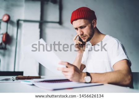 Side view of concentrated young male in red beanie sitting at table with paper in hand and talking on mobile phone