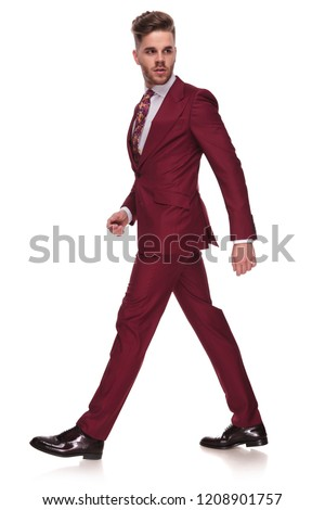 e9058792e506 side view of confident businessman in grena suit walking on white background  and looking behind,