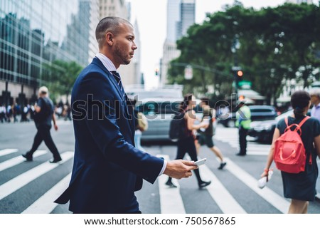 Side view of confident businessman passing crosswalk in modern district of megalopolis choosing direction, serious male entrepreneur crossing street with crowd getting to office building by foot