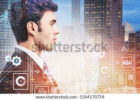 Side view of confident young businessman standing in night city with double exposure of infographics interface. Toned image #1564170754