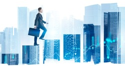 Side view of confident young businessman with briefcase climbing bar chart in abstract city with double exposure of blurry digital graphs. Concept of career ladder and stock market