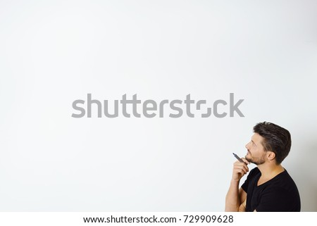 Side view of contemplative man holding marker pen standing by white wall with copy space