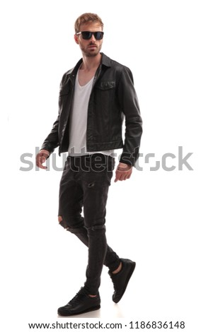 side view of cool young man with sunglasses and black leather jacket walking on white background, full length picture