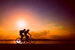 Side view of couple riding  on seashore with their bicycles. sunset sky on background. couple in love. silhouette of man and woman.