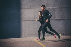 Side view of couple running in an urban environment