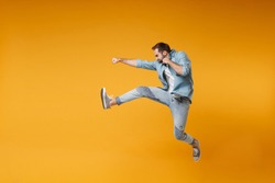 Side view of crazy young bearded man in casual blue shirt posing isolated on yellow orange background studio portrait. People sincere emotions lifestyle concept. Mock up copy space. Jumping, fighting
