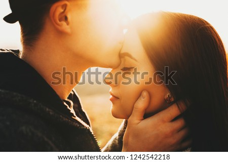 Side view of crop male kissing pretty girlfriend in forehead while spending time in nature on sunny day.Crop guy kissing girlfriend in forehead in nature