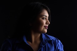 side view of dark portrait of a latin woman on black background, smiling