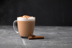 Side view of delicious cappuccino coffee with milk foam sprinkled with cinnamon in a transparent glass mug on a gray background, horizontal format