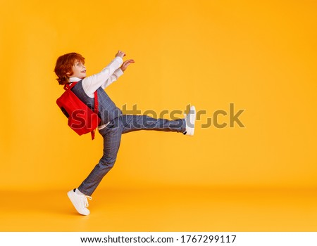 Side view of delighted schoolboy smiling and carrying textbooks while walking to school against yellow backdrop Stock photo ©